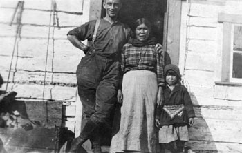 Claude Tidd posing with a First Nation woman and child, possibly at New Rampart House