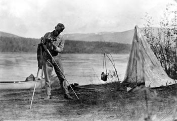 """Camera fiend takes a day off along the Yukon River. Rigging up the 'tele' lens. 1932"""