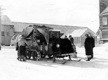 """Another mode of travel in the Yukon in winter. Mail and passengers leaving Mayo by snowmobile Spring 1936."""