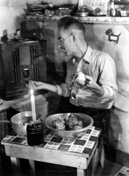 """Helping the cook."" Claude multi-tasks by peeling potatoes, tuning the radio, and smoking a cigar at the cabin in Twelve Mile. 1938"