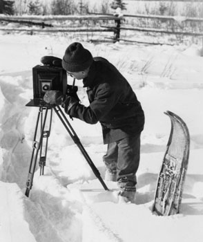 The intrepid photographer sets his camera up in the snow. Note the pipe, which seems to be present in more photos of Claude than not!