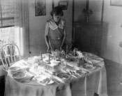 """Looks like a big night!"" Mary sets the table for a dinner party, 1933."