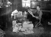 Claude opens his Christmas boxes in Mayo, 1933. Mary spent this Christmas in England with Claude's parents.